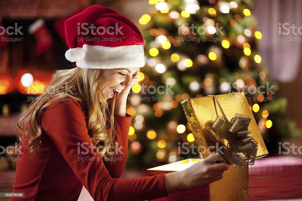 Ecstatic woman opening Christmas presents. stock photo