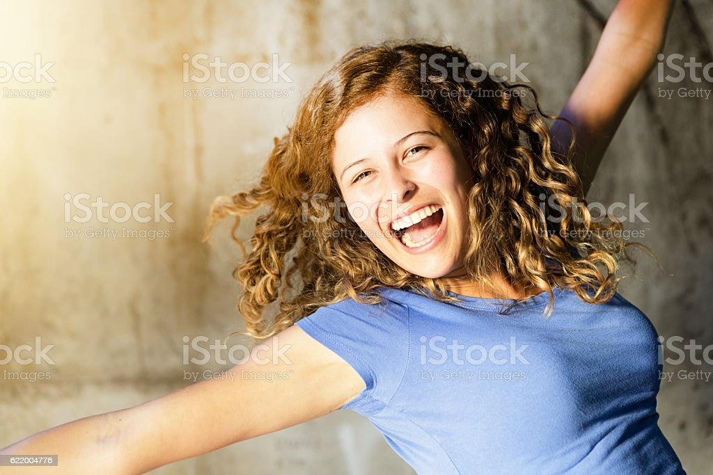 Ecstatic young curly-haired beauty gestures joyfully stock photo