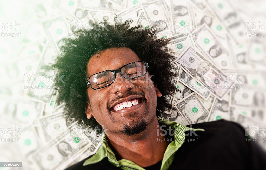 Ecstatic young man lies on pile of dollars grinning joyfully stock photo