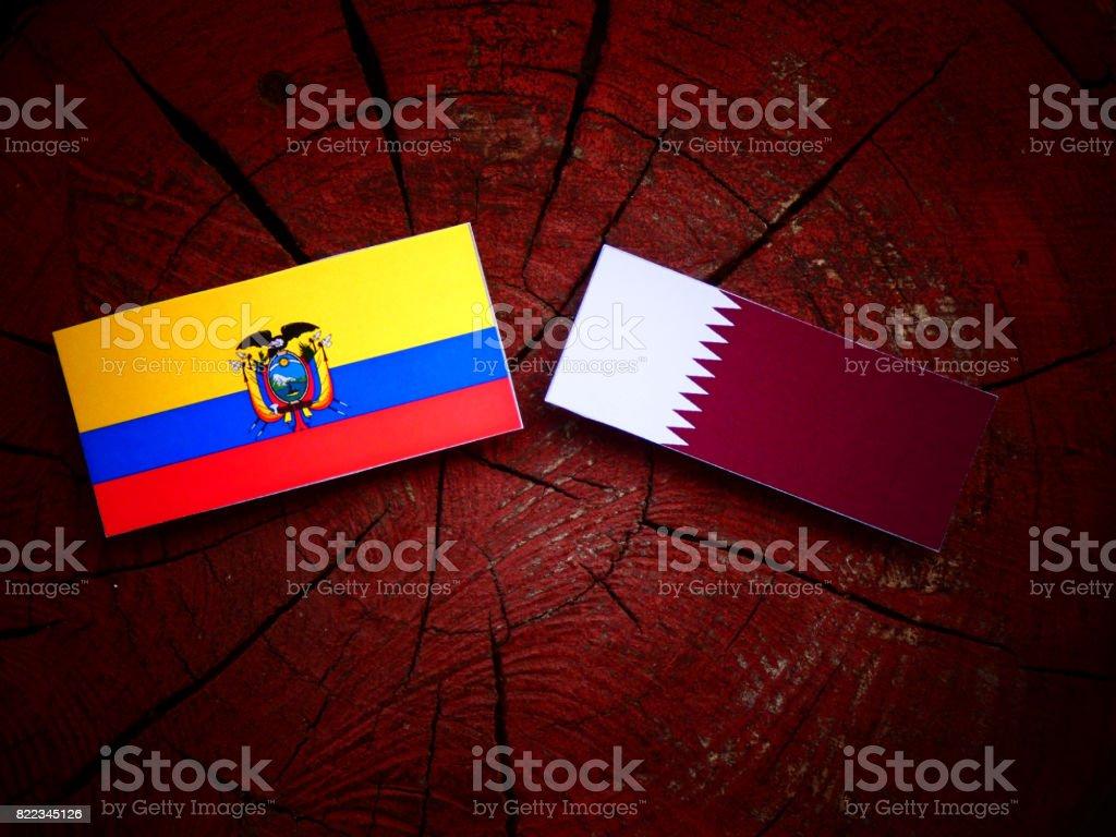 Ecuador flag with Qatari flag on a tree stump isolated stock photo