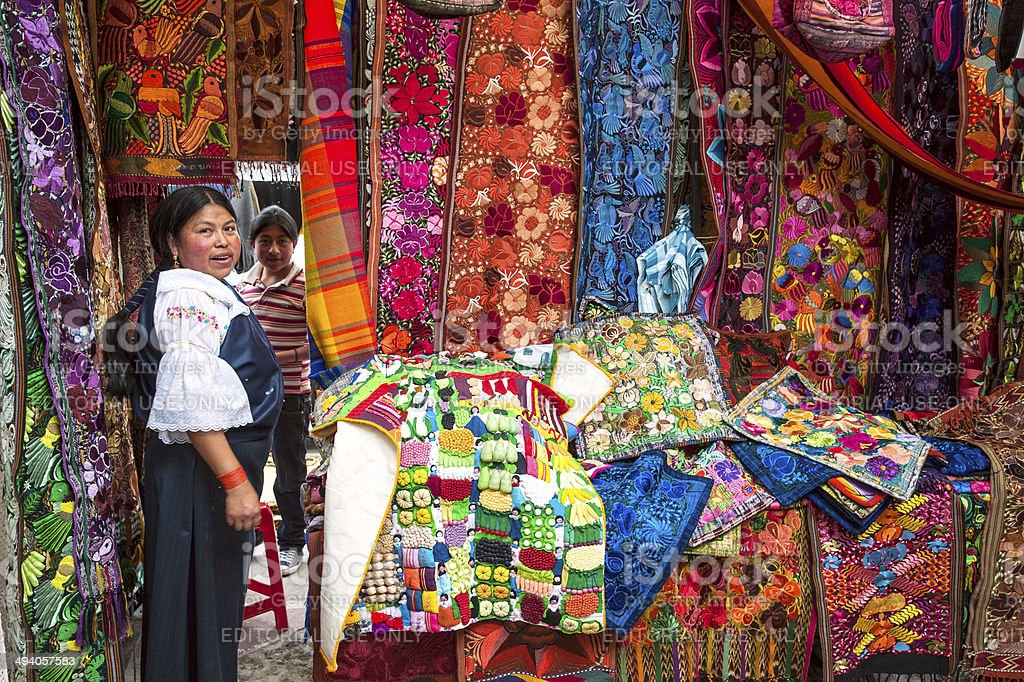Ecuador, Otavalo Indian woman sells products of weaving stock photo