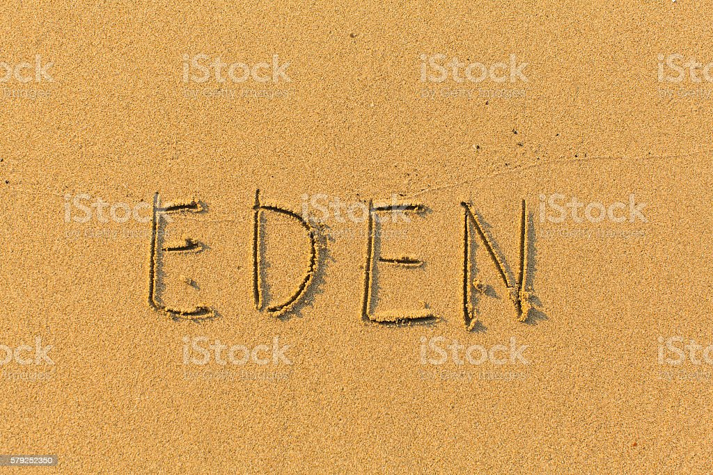 Eden - words hand-written on sand beach. stock photo
