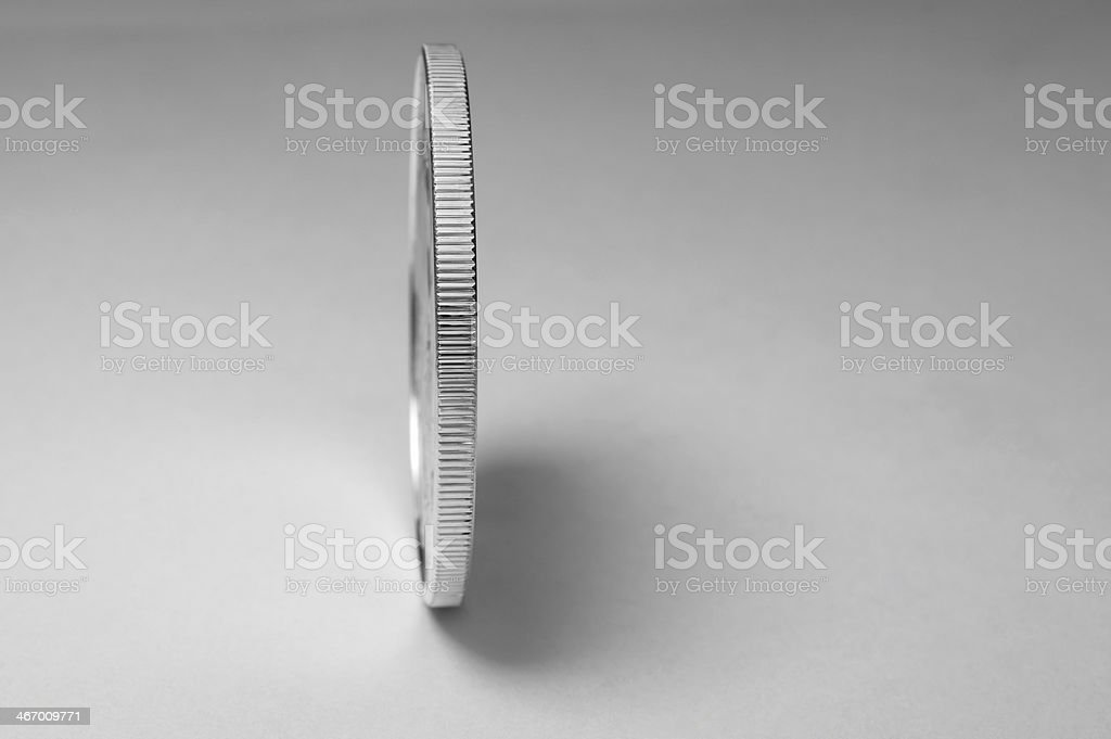 Edge of a silver colored coin balanced on end royalty-free stock photo