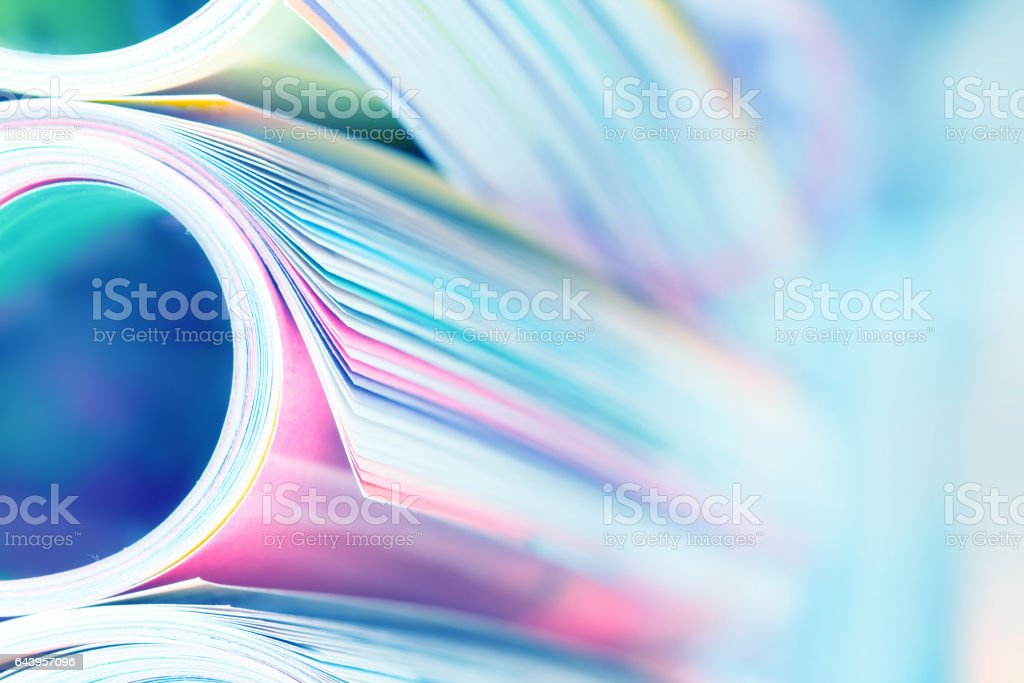 edge of colorful magazine stacking roll with  blurry bookshelf background stock photo