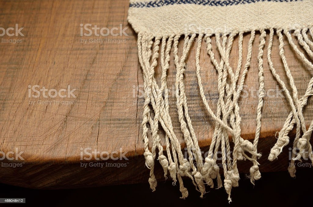 Edge of the wood table with a homespun towel stock photo