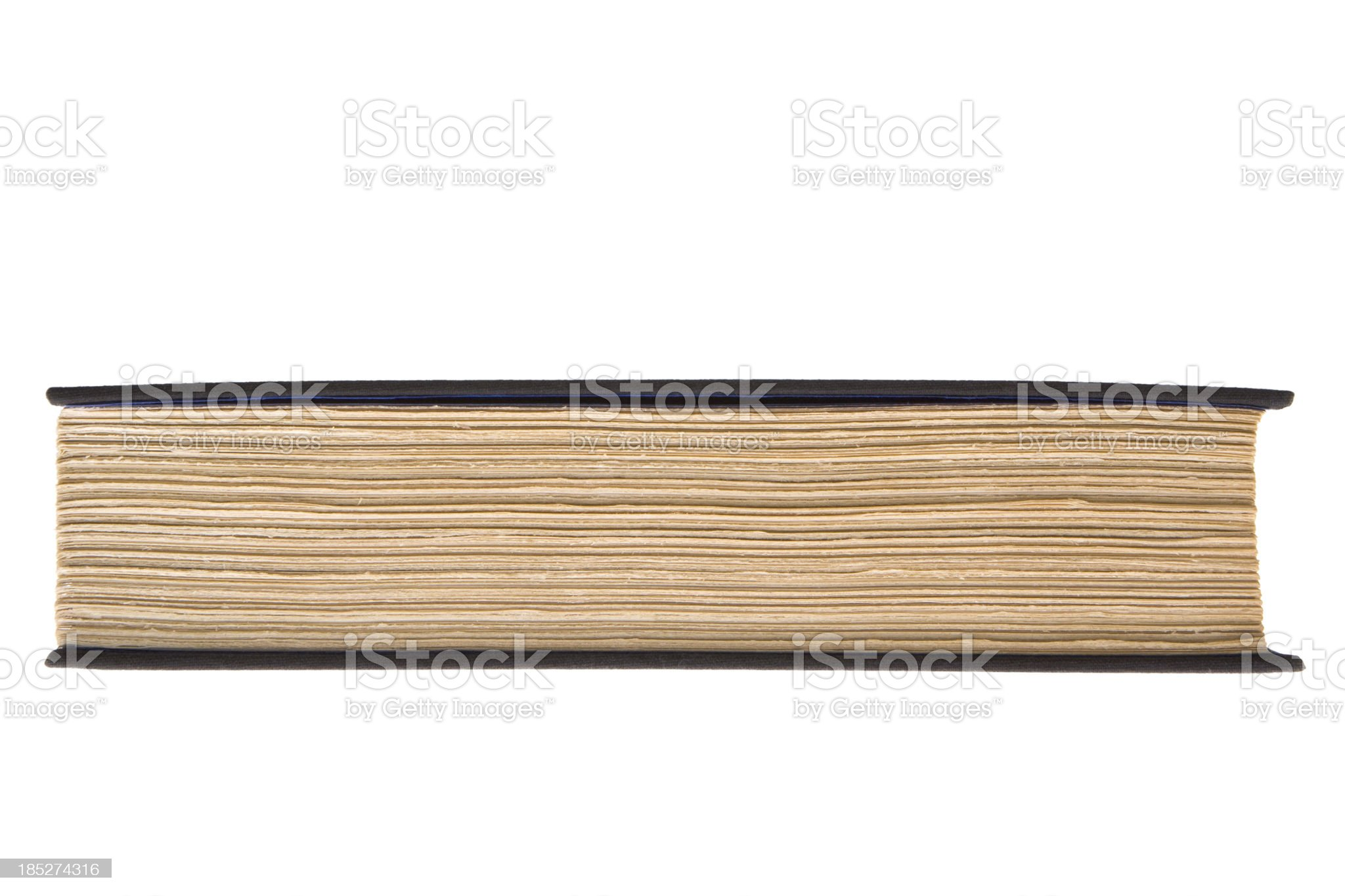 Edge view of old hardcover book with roughly trimmed pages royalty-free stock photo