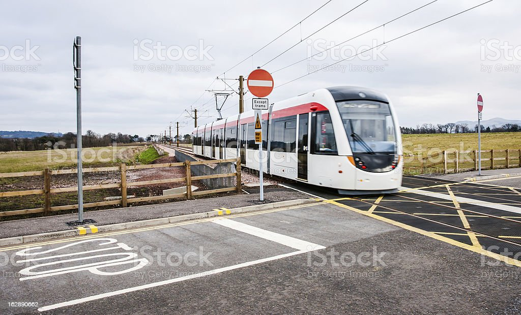 Edinburgh tram passes over unmanned level crossing stock photo