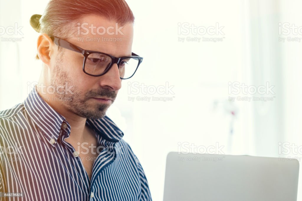 Editor-in-chief in blue shirt is working on a laptop stock photo