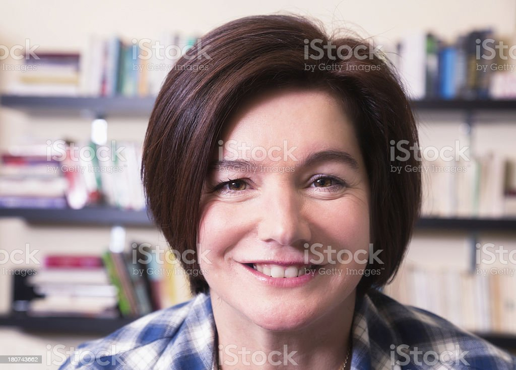 Educated mature woman close-up in front of bookshelf royalty-free stock photo