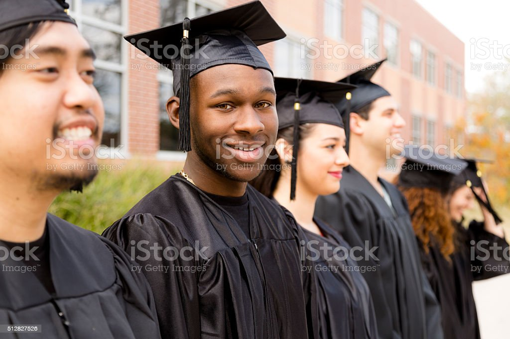 Education: African descent male graduate and friends on college campus. stock photo