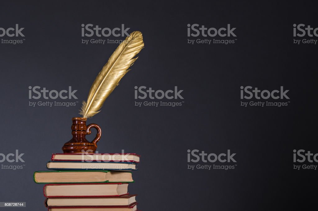 Education and information concept, literature and poetry idea. Books and inkwell with a golden quill pen on top stock photo