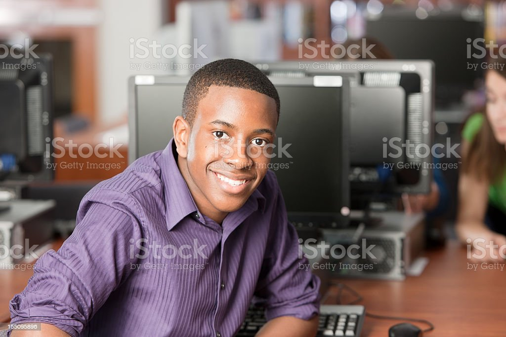Education: Black Teenage High School Student Using Computer in Library stock photo
