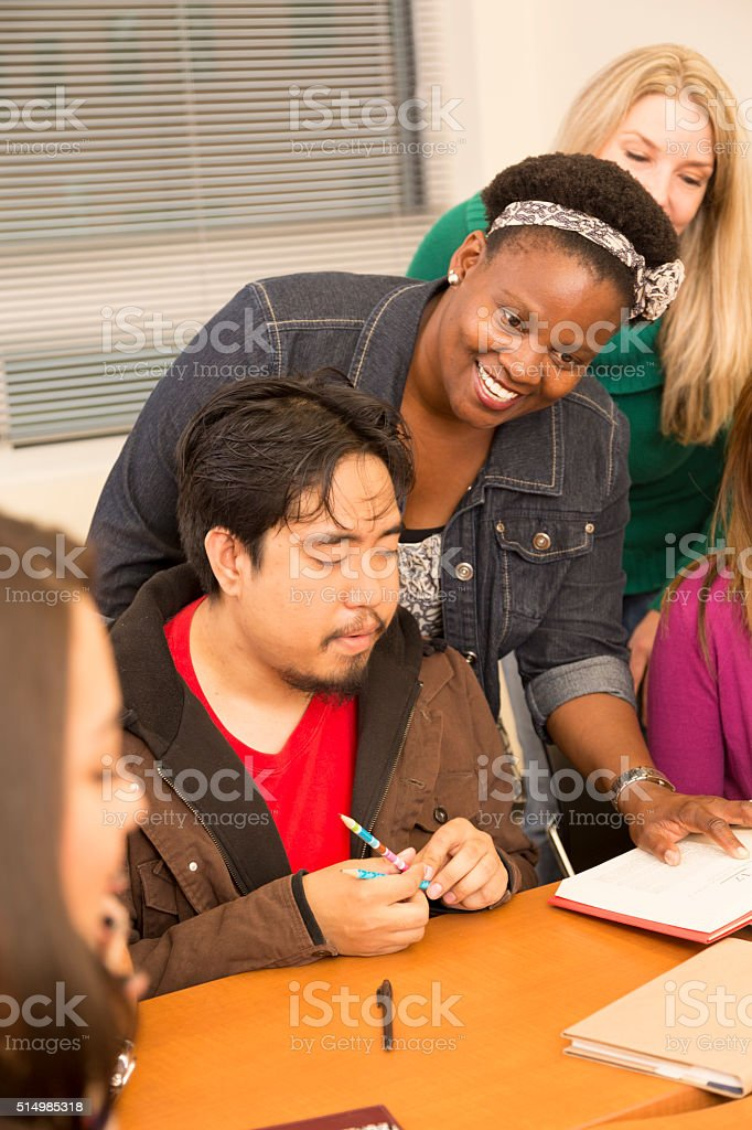 Education: College students, teacher collaborate in class. stock photo