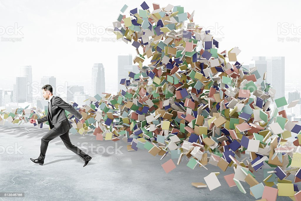Education concept with businessman runs from the mountain of boo stock photo