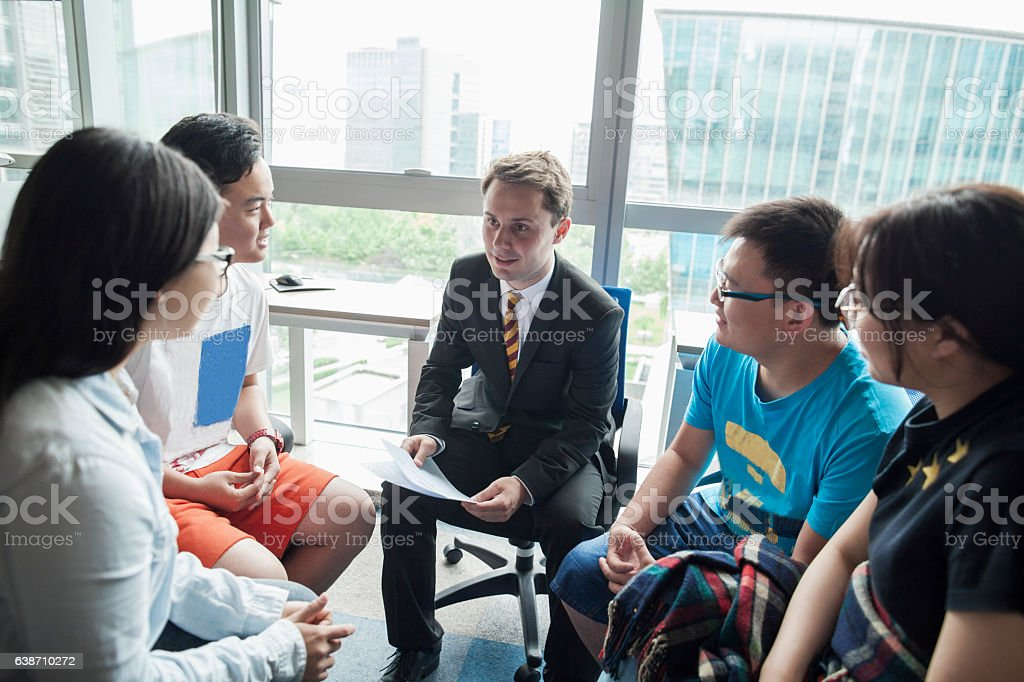 Education consultant with Chinese students in office stock photo