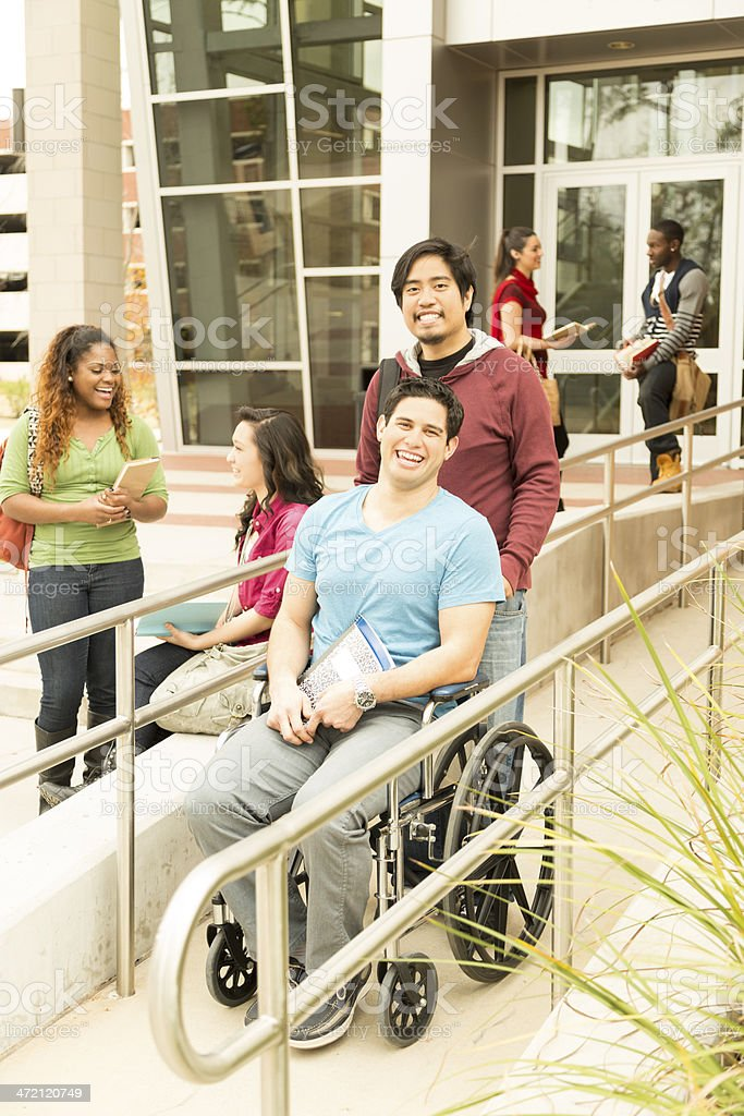 Education: Disabled student helped down wheelchair ramp. College campus. stock photo