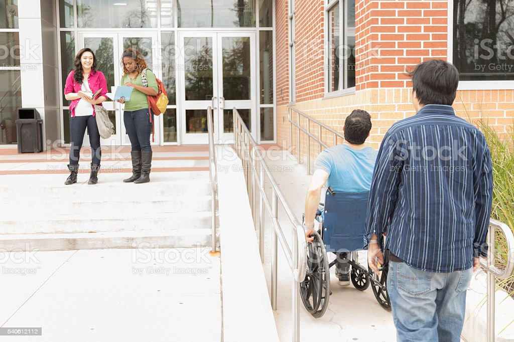 Education: Disabled student helped up wheelchair ramp. College campus. stock photo