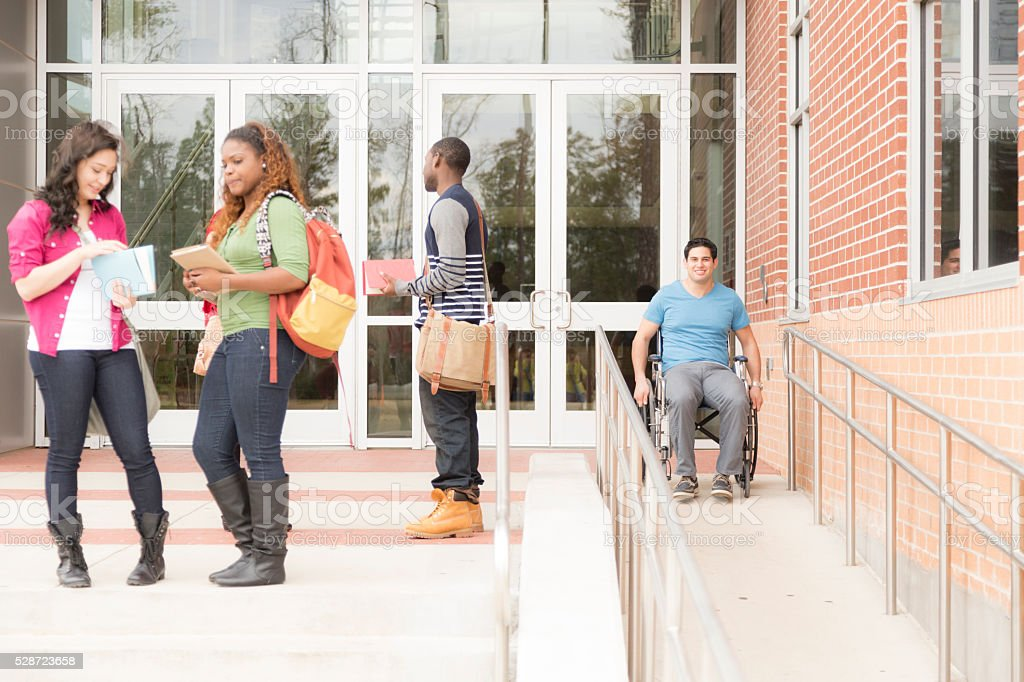 Education: Disabled student travels down wheelchair ramp. College campus. stock photo