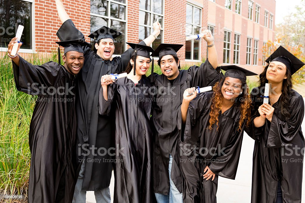 Six, multi-ethnic friends dressed in black cap and gowns excitedly...