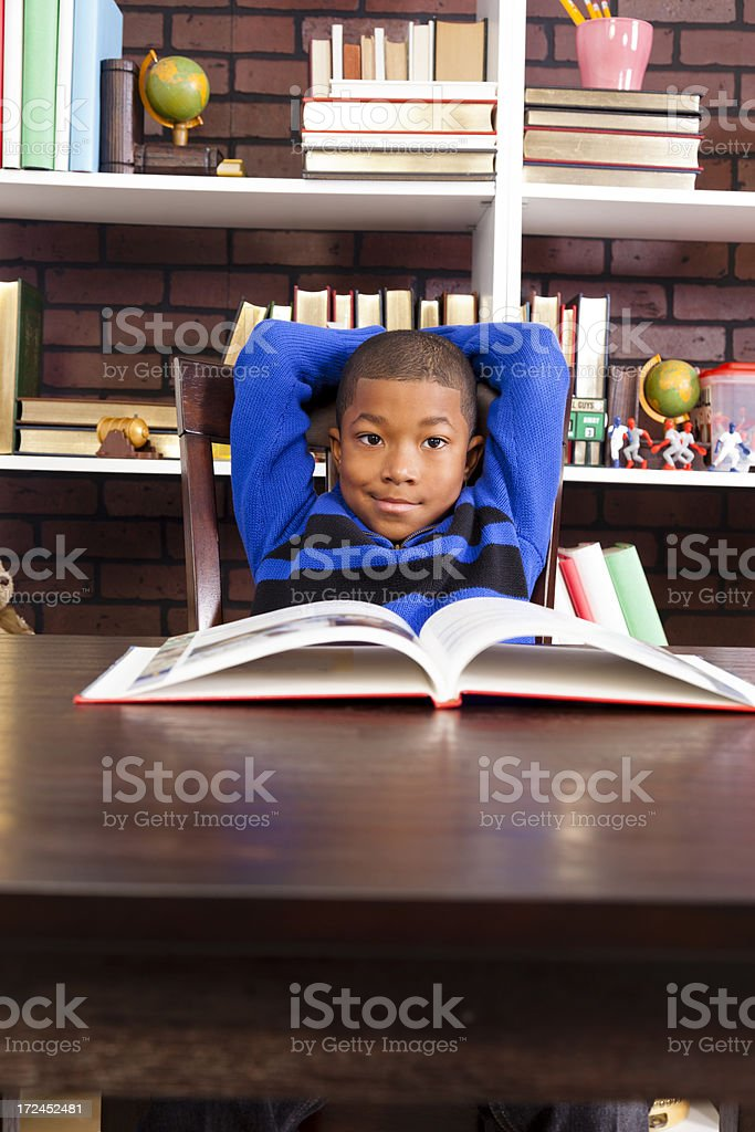 Education:  Elementary child in library with open book on table royalty-free stock photo