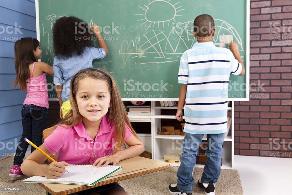 Education:  Elementary girl in classroom desk.  Chalkboard and students background. royalty-free stock photo