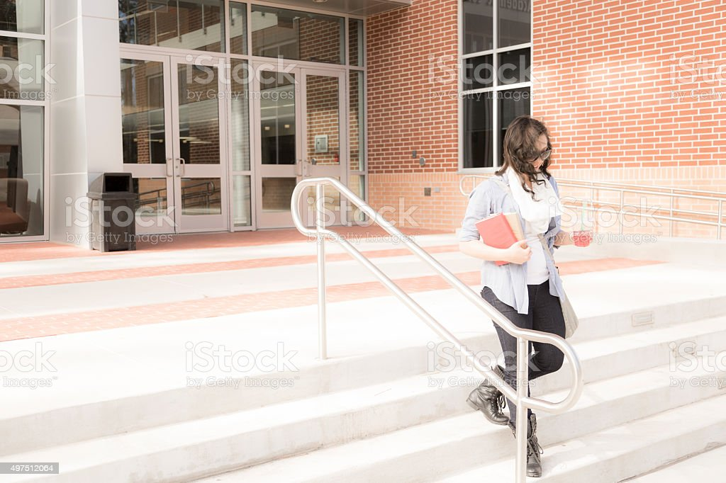 Education: Female college student leaving school building. stock photo