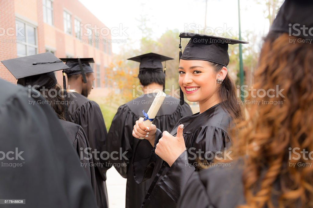 Education: Female graduate and friends on college campus. stock photo