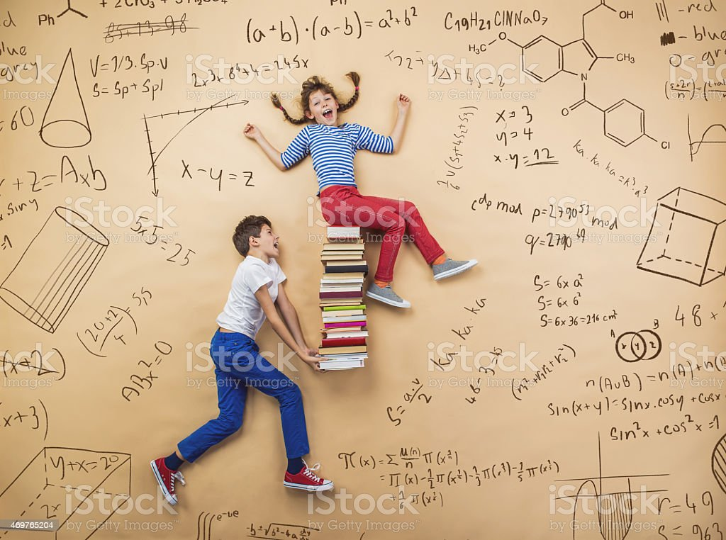 Education image of two schoolchildren on a math background stock photo