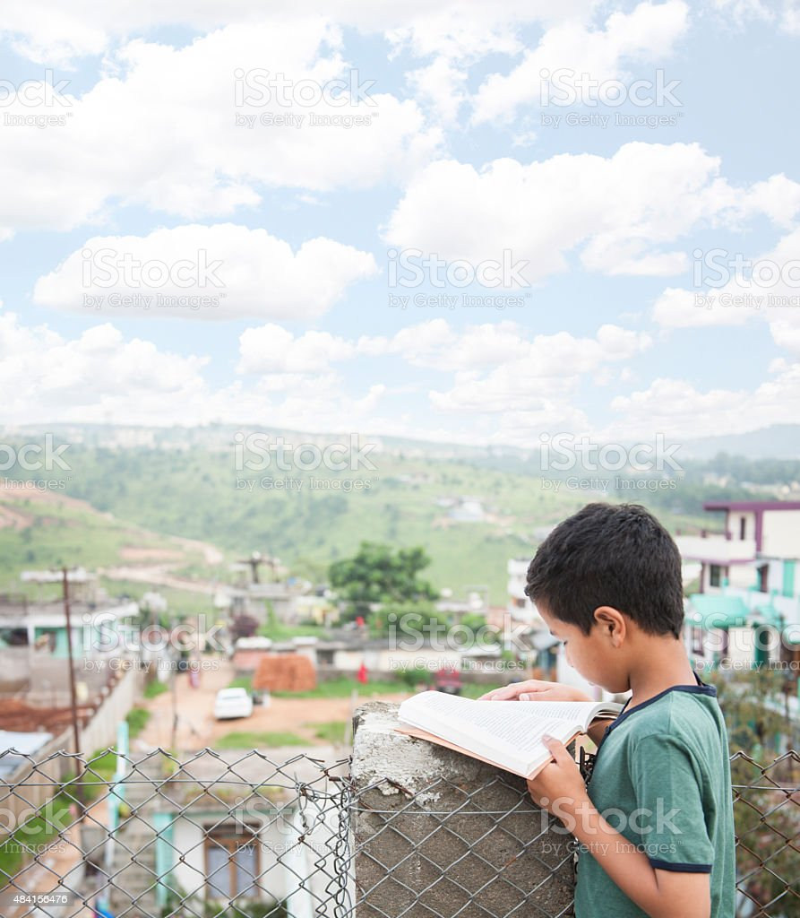 Education. Indian descent child reading, homework outdoors. stock photo