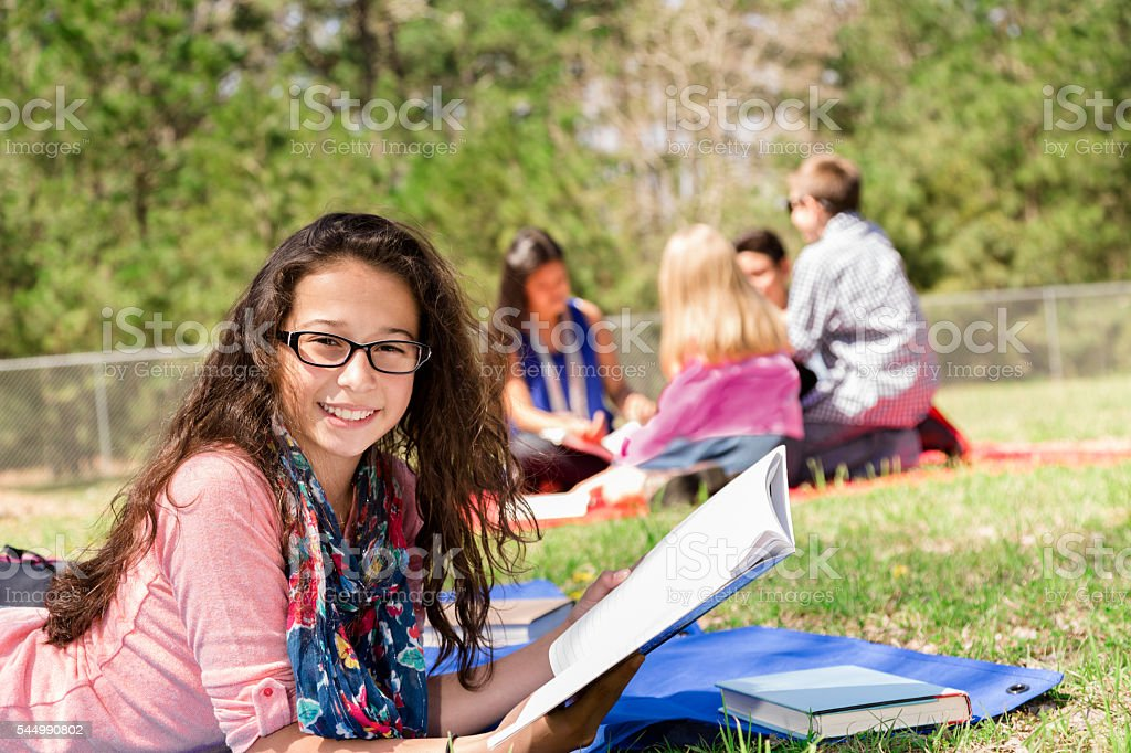 Education: Latin pre-teenage girl studies at local park. Friends background. stock photo