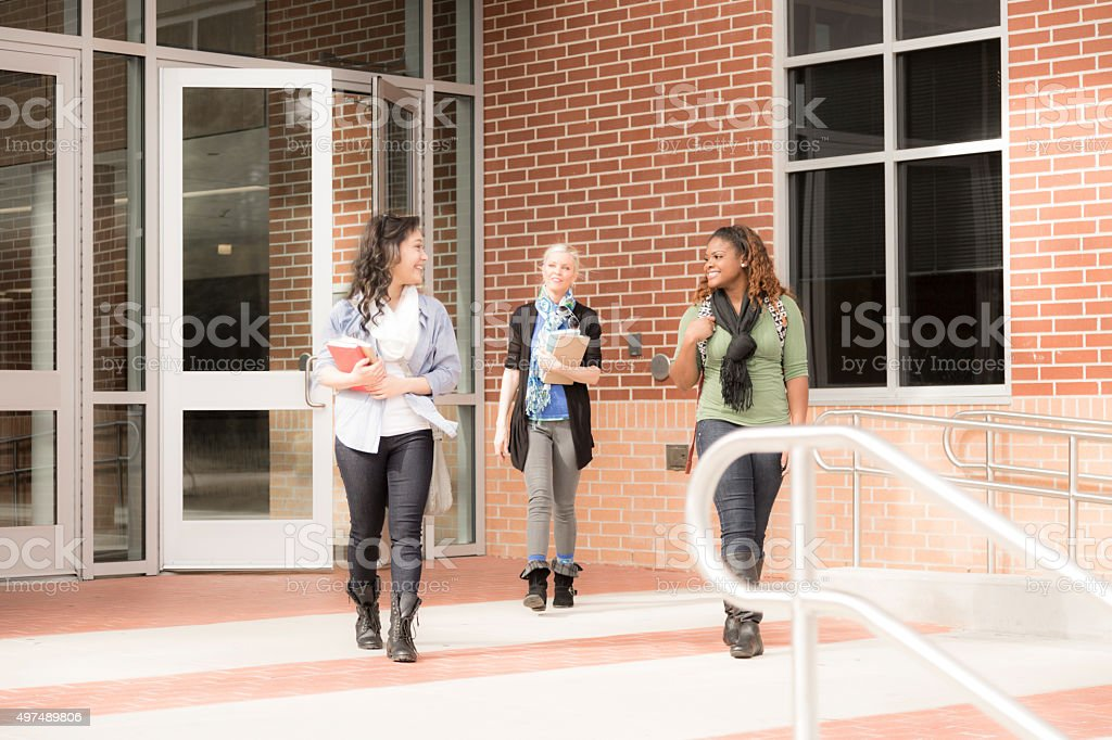 Multi-ethnic group of college students talk outside school building...