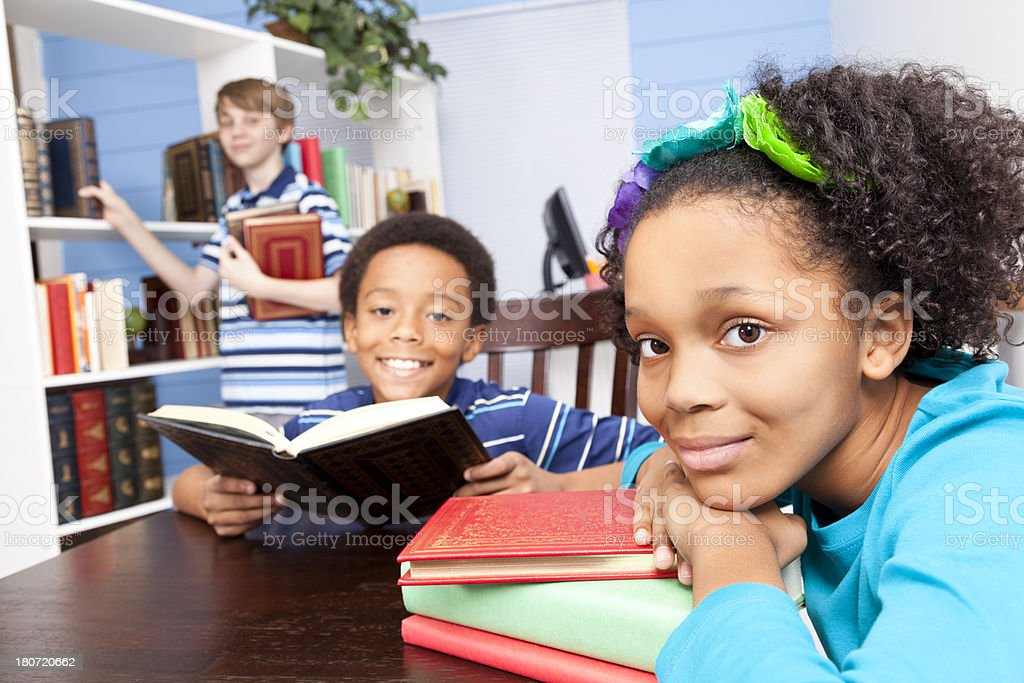Education:  Multi-ethnic Students junior high in library. Reading at table. royalty-free stock photo