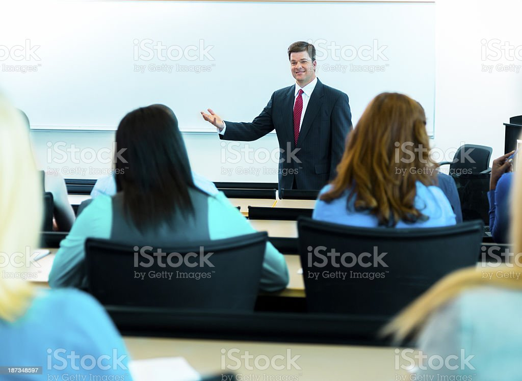 Education:  Professor in lecture hall gestures to his students. royalty-free stock photo