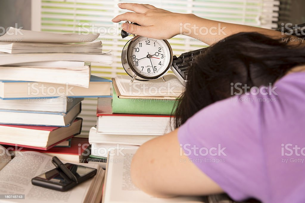 Education: Resting woman reaching for alarm clock on book stack royalty-free stock photo