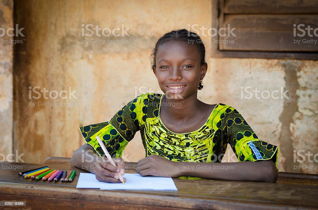 Education Schooling Symbol - Smiling Black Girl Drawing On Desk stock photo