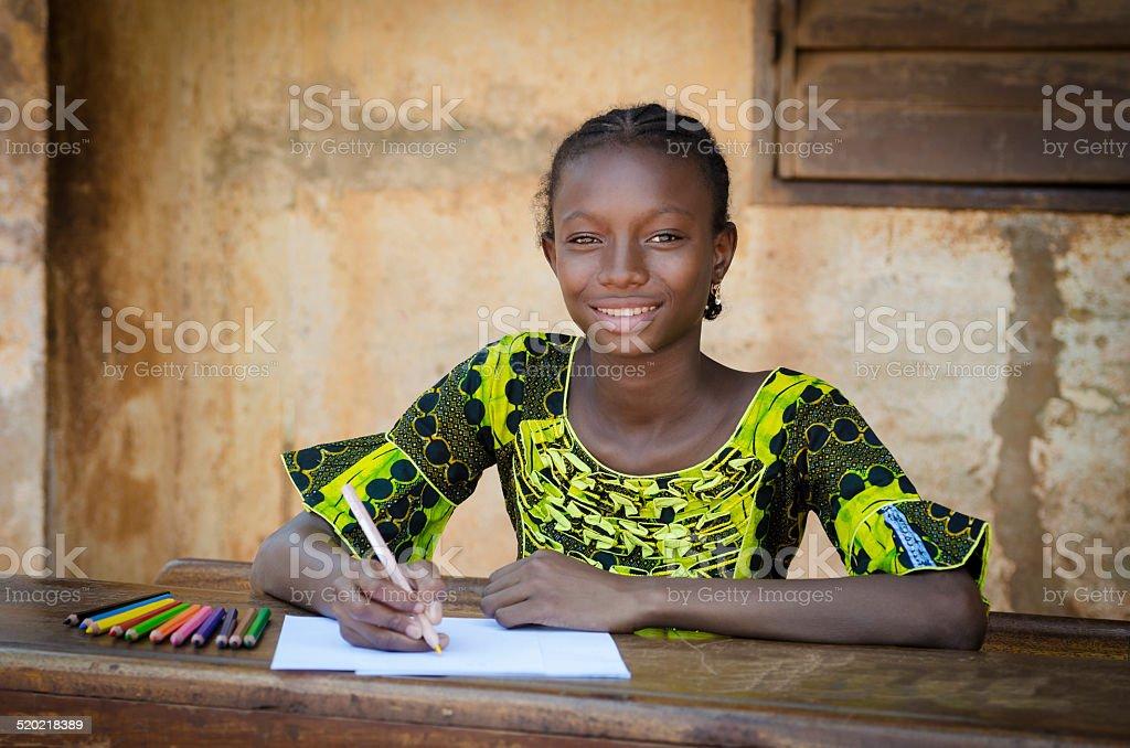 Education Schooling Symbol - Smiling Black Girl Drawing On Desk stock photo