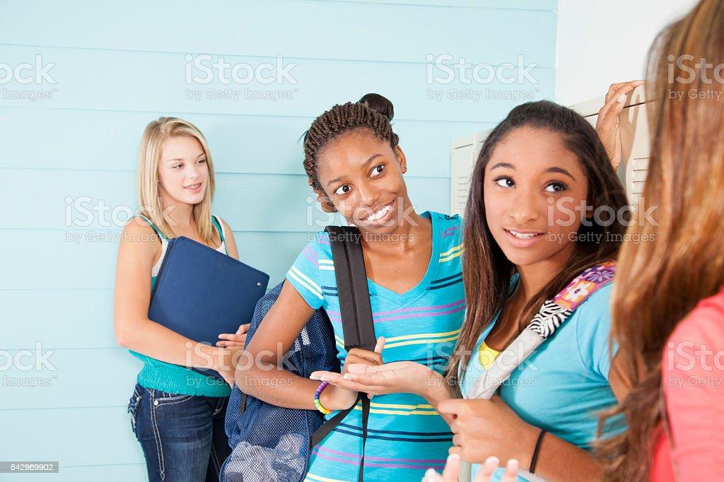 Education:  Teenage girl friends talk in school hall before class. stock photo