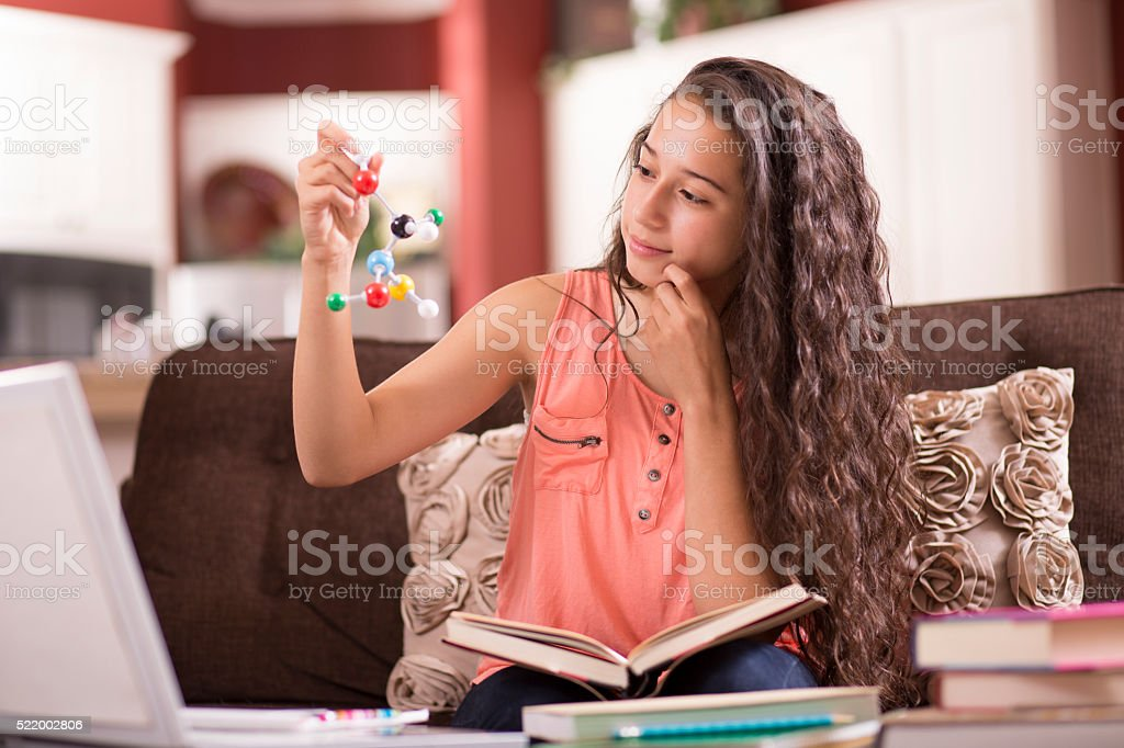 Education.  Teenage girl studying DNA molecule, science at home. Homework. stock photo