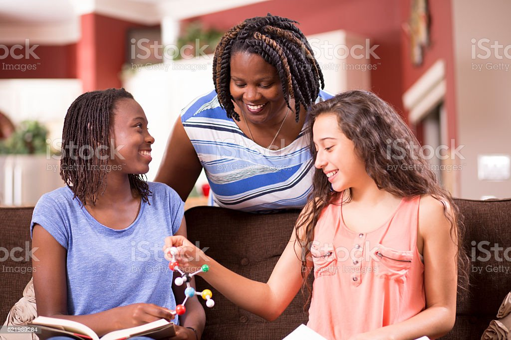 Education.  Teenage girls studying DNA molecule, science at home. Homework. stock photo