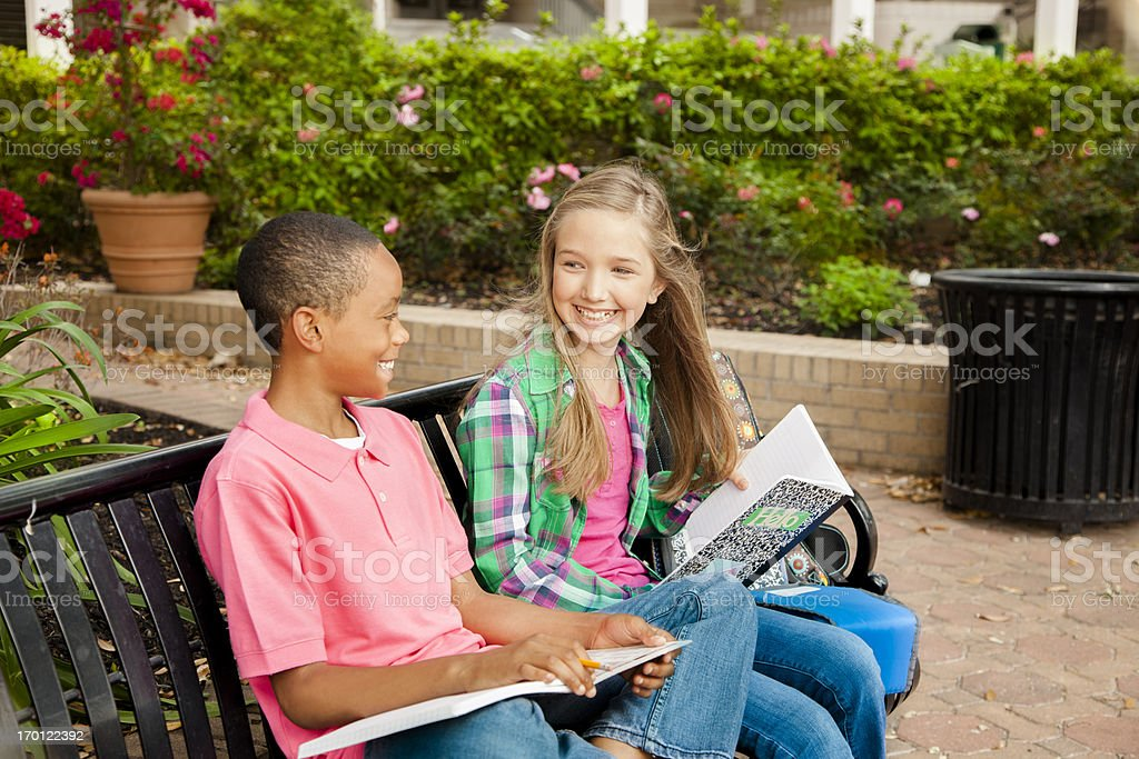 Education: Two elementary students waiting on a bench. royalty-free stock photo