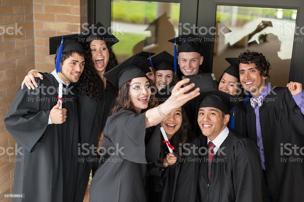 Diverse group of college friends excited after graduation taking a...
