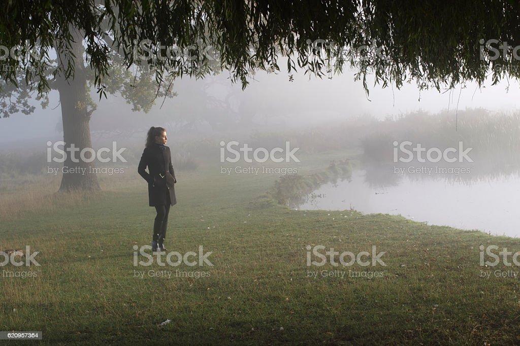 Eerie misty river scene Russian outdoor girl stock photo