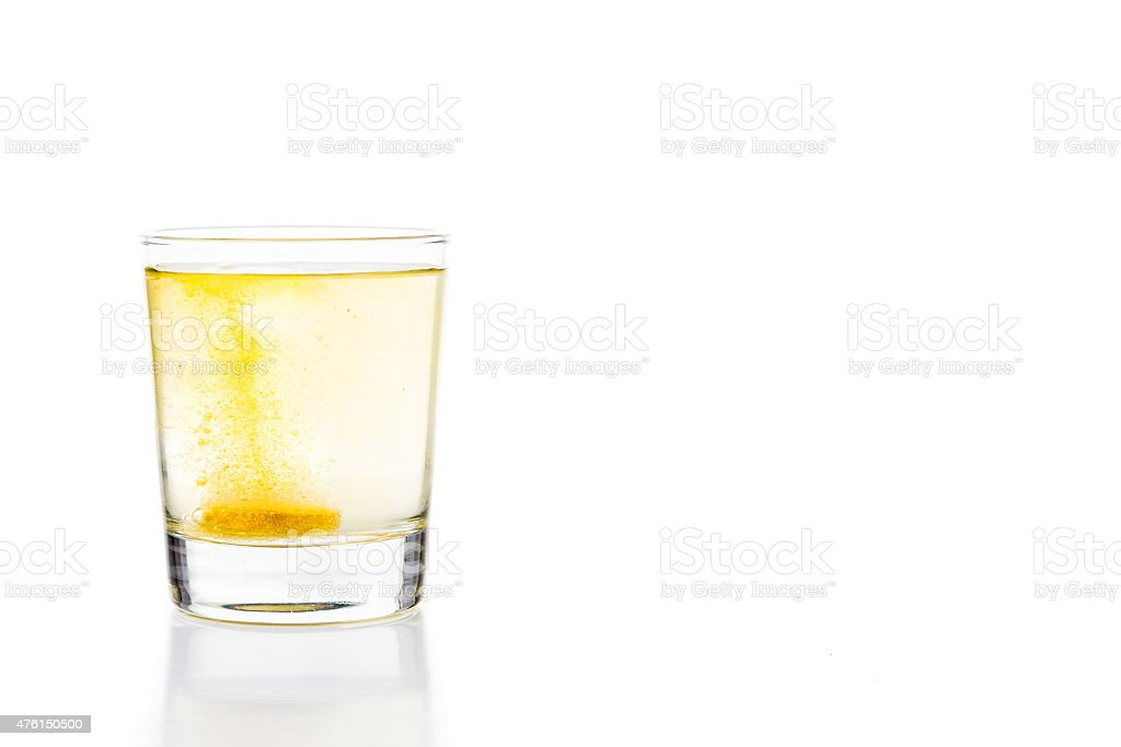 Effervescent vitamin C tablet bubbles in glass of water stock photo