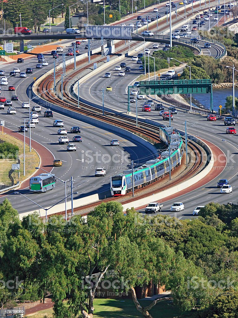 Efficient city transport: train down freeway median strip stock photo