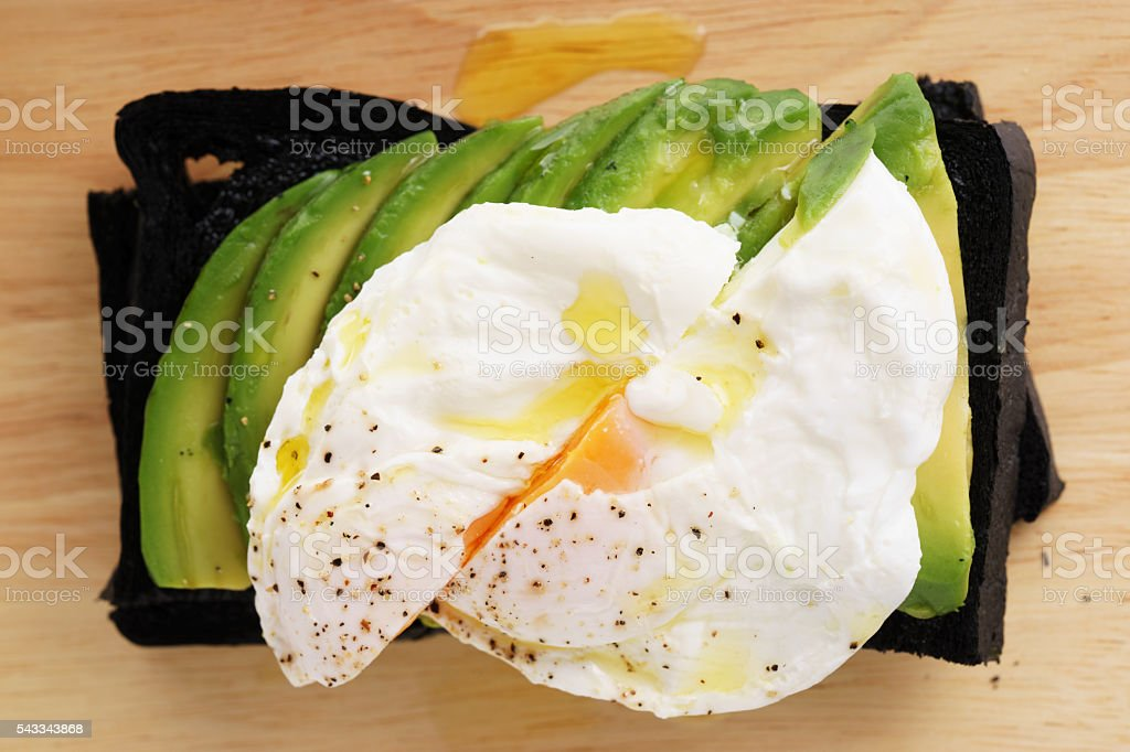 egg and avocado charcoal bread toast stock photo