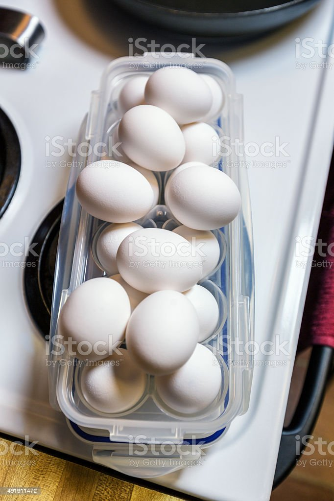 Egg Container Eggs Piled Up On Electric Stove stock photo