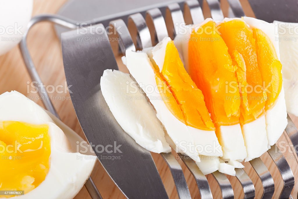 Egg cutter and cutted eggs on wooden board royalty-free stock photo