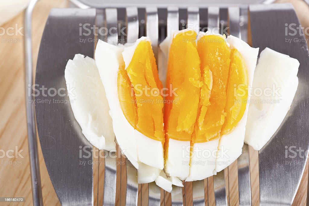 Egg cutter and cutted eggs on wooden table royalty-free stock photo