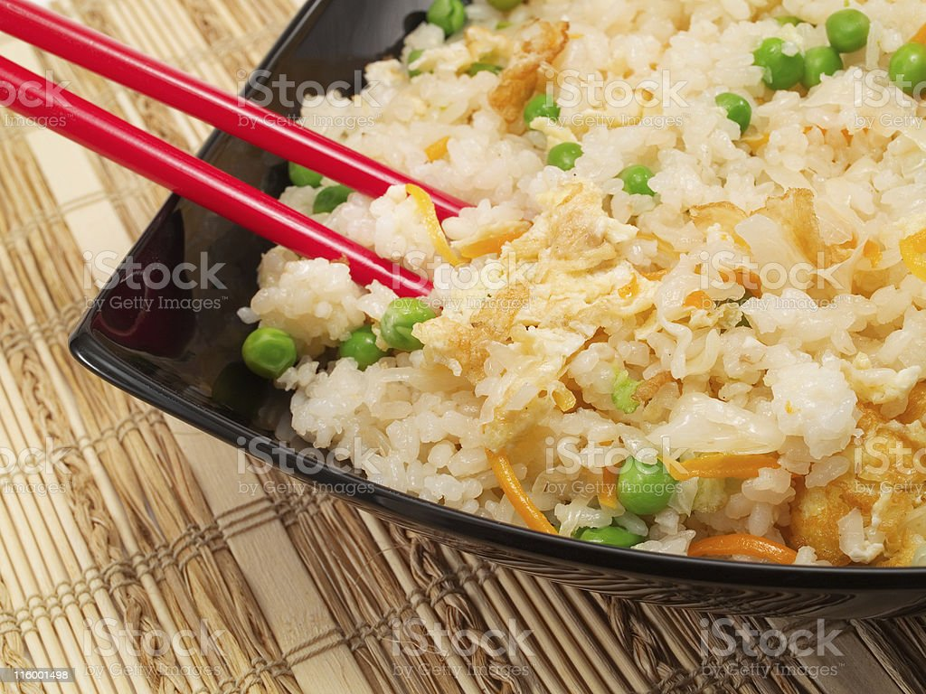 Egg fried rice with peas on a black plate with chopsticks royalty-free stock photo