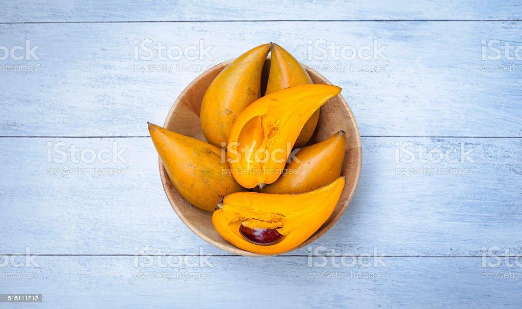 Egg fruit in wooden bowl on white wooden floor stock photo